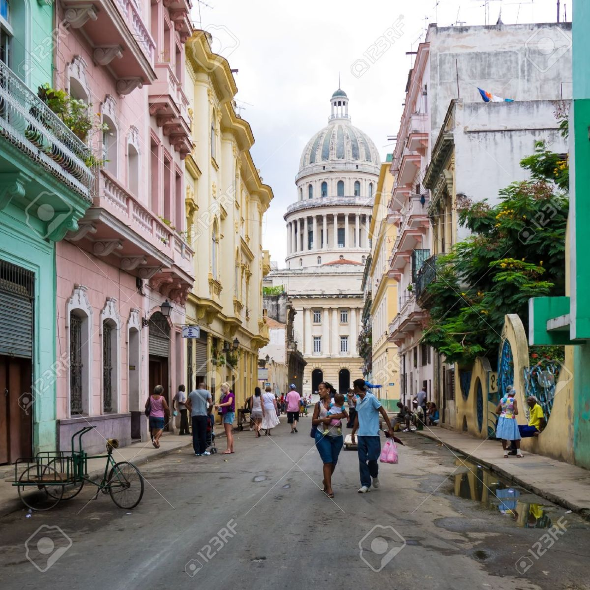 15294819-Cuban-people-in-a-street-leading-to-the-Capitol-in-Havana-Stock-Photo