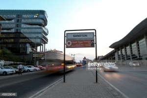 A Sandton sign stands on a central reservation between the offices of EY, operated by Ernst & Young Global Ltd., left, and the Gautrain station, right, in Sandton, South Africa, on Tuesday, Sept. 23, 2014. Sandton, once a single 20-story tower and a shopping mall, is also set to displace Johannesburg's city center to become South Africa's largest commercial hub. Photographer: Dean Hutton/Bloomberg