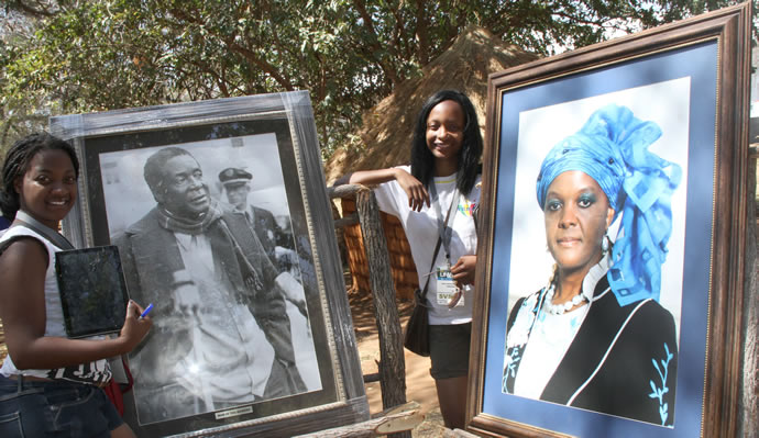 Danai-Pawandiwa-and-Tapiwa-Kupfuwa-at-the-potraits-of-President-Mugabe-and-First-Lady-Amai-Grace-at-the-Zimbabwe-cultural-centre