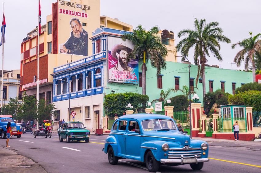 Street with oldtimers and propaganda in Santiago de Cuba