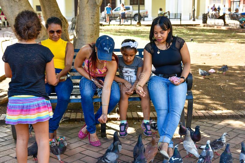 santo-domingo-dominican-republic-women-feeds-pigeons-columbus-park-colonial-zone-santo-domingo-78427276