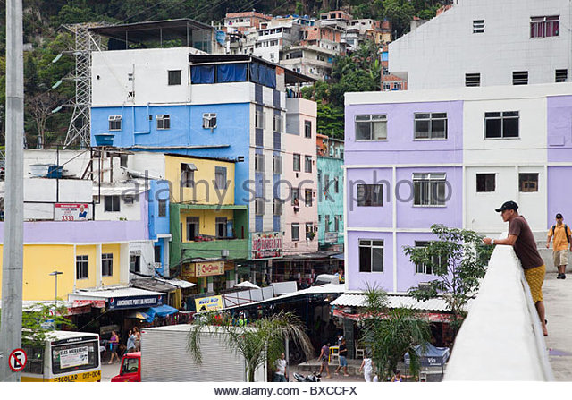 a-man-looks-out-from-a-bridge-that-crosses-into-the-rocinha-favela-bxccfx
